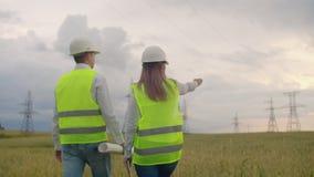 Un elettricista nei campi vicino all'elettrodotto L'elettricista dirige il processo di costruzione del potere archivi video