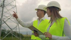 Un elettricista nei campi vicino all'elettrodotto L'elettricista dirige il processo di costruzione del potere video d archivio