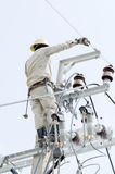Un elettricista sta riparando il cavo sul palo di energia elettrica Fotografia Stock
