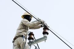 Un elettricista sta riparando il cavo sul palo di energia elettrica Fotografie Stock Libere da Diritti