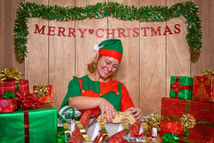 Un elfo che avvolge i regali di Natale nel polo nord Immagini Stock Libere da Diritti