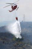 Un elicottero del pompiere getta l'acqua su un fuoco immagini stock libere da diritti