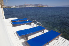 Un embarcadero de madera blanco en el cual cuatro caballetes azules de la playa por el mar Fotografía de archivo libre de regalías