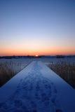 Un embarcadero por un lago congelado en la puesta del sol Imagenes de archivo