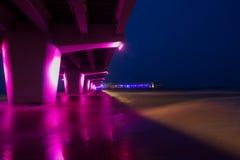 Un embarcadero rosado iluminado en la orilla del mar Báltico fotos de archivo