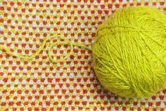 Un embrouillement de fil vert et de laine sur un fond de tissu tricoté et de laine Images stock