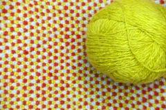 Un embrouillement de fil vert et de laine sur un fond de tissu tricoté et de laine Photo stock
