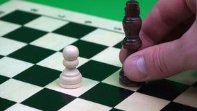 Un empeño blanco es cortado por un rey negro en un tablero de ajedrez metrajes