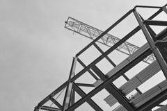 Un emplazamiento de la obra con enmarcar del acero y una grúa de construcción amarilla Imagen de archivo