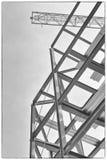 Un emplazamiento de la obra con enmarcar del acero y una grúa de construcción amarilla Foto de archivo libre de regalías