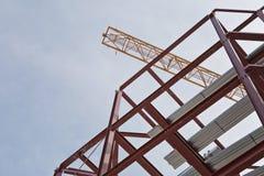 Un emplazamiento de la obra con enmarcar del acero y una grúa de construcción amarilla Imagen de archivo libre de regalías