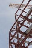 Un emplazamiento de la obra con enmarcar del acero y una grúa de construcción amarilla Imagenes de archivo