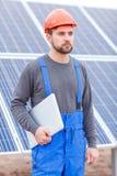 Un empleado de la estación de la batería solar mira en alguna parte y sosteniendo el ordenador portátil outdoors Fotografía de archivo