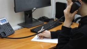 Un empleado joven de la oficina habla en su teléfono del trabajo y anota la información importante en problemas de resolución almacen de metraje de vídeo