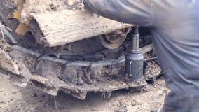 Un empleado repara una niveladora Reparación del equipo de construcción pesado en el emplazamiento de la obra metrajes