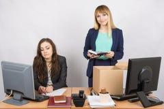 Un employé dans le bureau met heureusement des choses hors de la boîte à côté d'un collègue Image libre de droits
