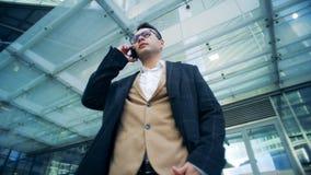 Un empresario está teniendo un phonecall serio en el medio de un complejo del negocio Cantidad épica roja de la cámara del cine