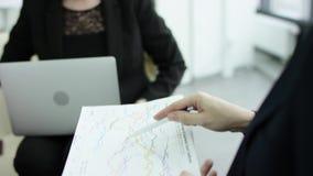 Un encargado de sexo femenino presenta nuevo plan del proyecto a los colegas en el encuentro, explicando ideas en flipchart a los almacen de video