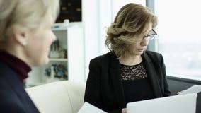 Un encargado de sexo femenino presenta nuevo plan del proyecto a los colegas en el encuentro, explicando ideas en flipchart a los metrajes