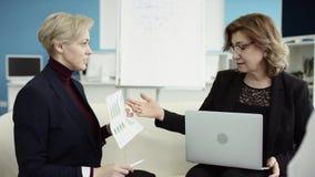 Un encargado de sexo femenino presenta nuevo plan del proyecto a los colegas en el encuentro, explicando ideas en flipchart a los almacen de metraje de vídeo