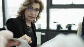 Un encargado de sexo femenino presenta nuevo plan del proyecto a los colegas en el encuentro en la oficina, empresaria da la pres almacen de video