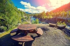 Un endroit au repos sur la banque de la rivière de montagne près du pont image libre de droits