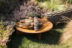 Un endroit pour un feu dans le jardin, le bois de chauffage sec et les fleurs image libre de droits