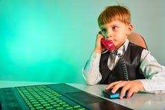 Un enfant à un ordinateur portable dans le bureau convient sur les sujets par le fil, le concept des affaires des enfants moderne images libres de droits