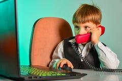 Un enfant à un ordinateur portable dans le bureau convient sur les sujets par le fil, le concept des affaires des enfants moderne images stock