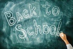 Un enfant écrit avec une craie sur un tableau noir De nouveau au fond d'école (EPS+JPG) Photographie stock