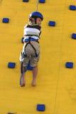 Un enfant abseilling en bas d'un mur s'élevant image stock