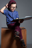 Un enfant aux yeux bleus avec des verres Un garçon s'assied avec si sérieux Image libre de droits