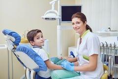 Un enfant avec un dentiste dans un bureau dentaire image libre de droits