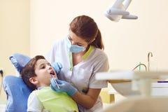 Un enfant avec un dentiste dans un bureau dentaire image stock