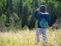 Un enfant avec un sac à dos marche à pied Photo libre de droits