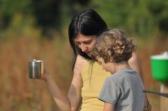 Un enfant avec une mère Le garçon et la femme boivent d'un thé cuvette Images stock
