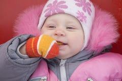 Un enfant avec une mitaine dans votre bouche Photographie stock libre de droits