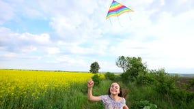 Un enfant court par un pré avec un cerf-volant banque de vidéos