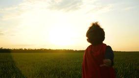 Un enfant dans un costume de super héros court à travers l'herbe verte sur un fond de coucher du soleil banque de vidéos