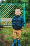 Un enfant dans le village se tient à la porte et sourit image stock