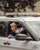 Un enfant dans une voiture de police sur un tour le long Photo stock