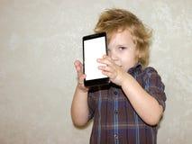 Un enfant de garçon regarde dans la caméra d'un smartphone, montre l'écran avec sa photo numérique image stock