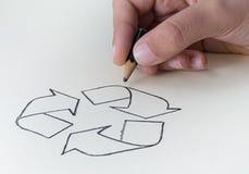 Un enfant dessinant le symbole de réutilisation avec un St très court de crayon Image stock