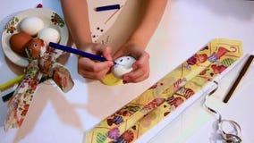 Un enfant dessine un visage drôle sur un oeuf blanc Décoration pour Pâques Fin vers le haut clips vidéos