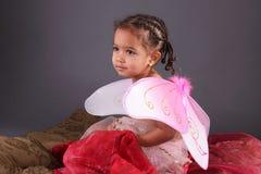 Un enfant en bas âge dans des ailes féeriques roses Photographie stock libre de droits