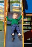 Un enfant en bas âge an de bébé garçon utilisant le chandail vert au terrain de jeu Photo libre de droits