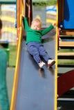 Un enfant en bas âge an de bébé garçon utilisant le chandail vert au terrain de jeu Photo stock