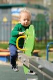 Un enfant en bas âge an de bébé garçon utilisant le chandail vert au terrain de jeu Image stock