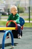 Un enfant en bas âge an de bébé garçon utilisant le chandail vert au terrain de jeu Photographie stock