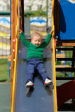 Un enfant en bas âge an de bébé garçon utilisant le chandail vert au terrain de jeu Photographie stock libre de droits
